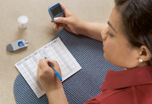 Woman holding glucometer and writing in blood glucose log.