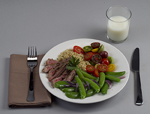 Dinner plate with balanced portions of meat, vegetables, and starch, with glass of milk.
