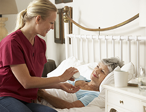 Healthcare provider giving woman medication in bed.